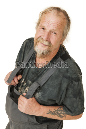older worker in dungarees on white