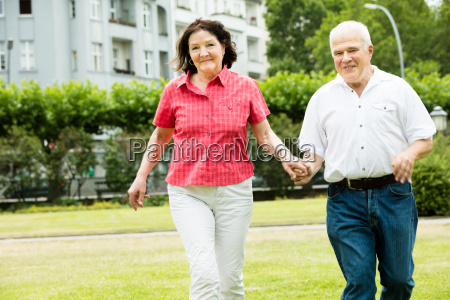 couple running in park holding hands