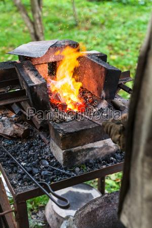 schmied erhitzt stahlstange im schmiedeofen