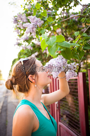 beautiful young woman smelling white jasmin