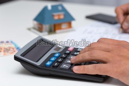 hand on calculator calculating household