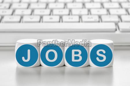 buchstabenwuerfel vor einer tastatur jobs