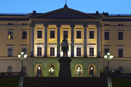 royal palace illuminated at dusk oslo