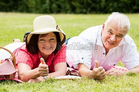 senior couple lying in park