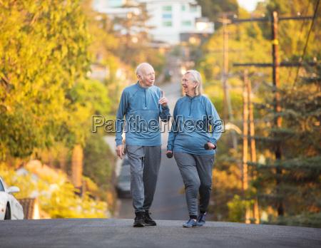 senior couple walking along street on