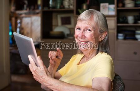 cute senior woman using tablet computer