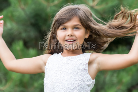 llittle girl with flowing hair outdoors