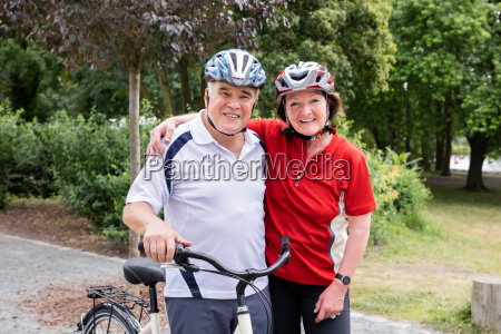 portrait of smiling couple with bicycle