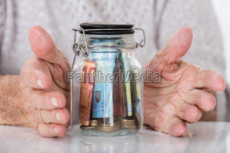 senior womans hand protecting money jar