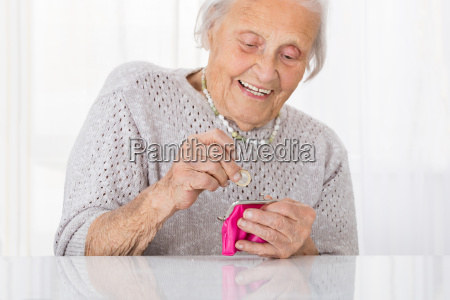 senior woman inserting coin in purse