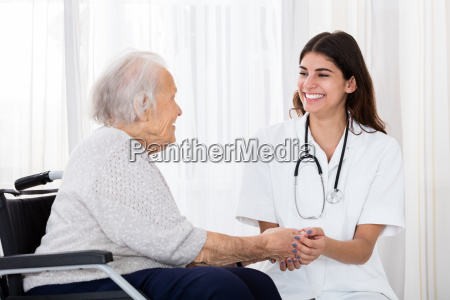 female doctor holding hands of disabled