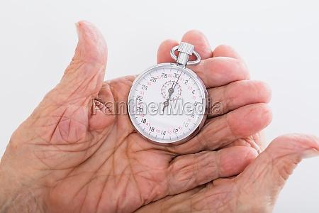 senior woman holding stop watch