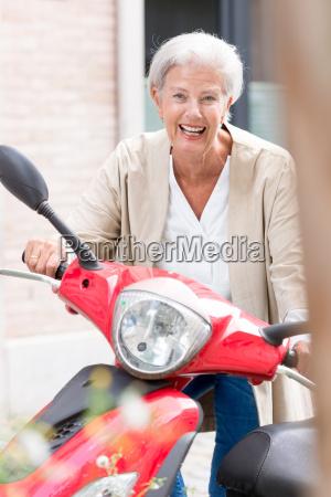 seniorin auf motorroller