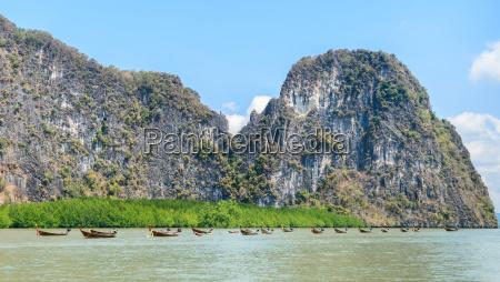 kalkstein insel mit mangrovenwald und longtail