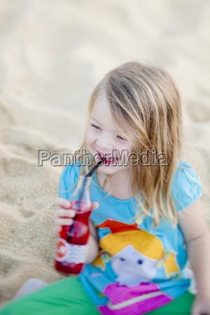 glueckliches maedchen am strand trinkt saft