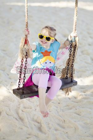 glueckliches maedchen schaukelt am strand