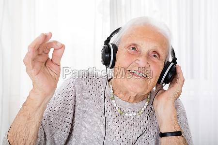 aeltere frau mit kopfhoerer musik geniesst