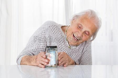 happy senior woman looking at money