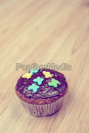 chocolate muffin on wooden ground