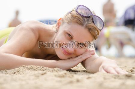 young girl lying on sandy beach