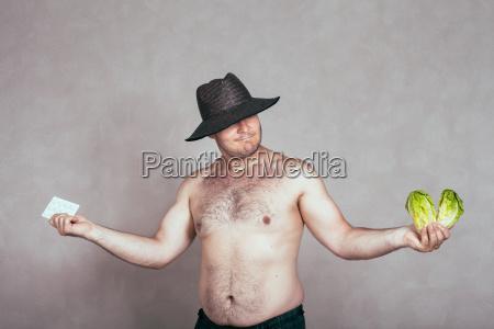 unentschlossener nackter korpulenter mann mit pharmazeutika
