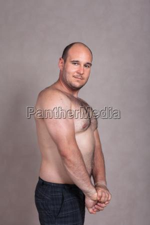 hemdloser mann zeigt seinen trizeps und