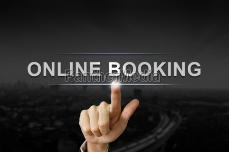 business hand pushing online booking button