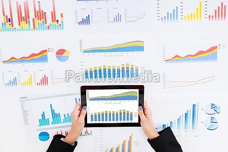 empresaria analizando graficos financieros utilizando tableta