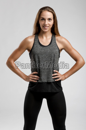 young fitness woman against a gray