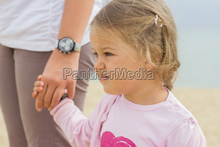 little girl hold mother hand