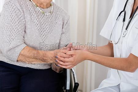 female doctor consoling senior patient
