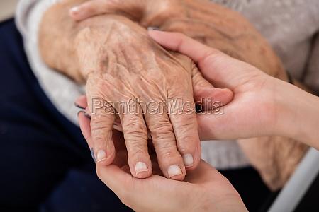 female doctor holding hand of senior