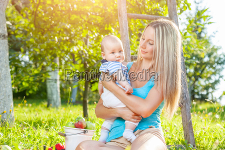 beautiful mother with baby sitting outdoors
