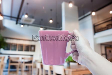 frau haelt kaffeetasse mit abstrakten unschaerfe