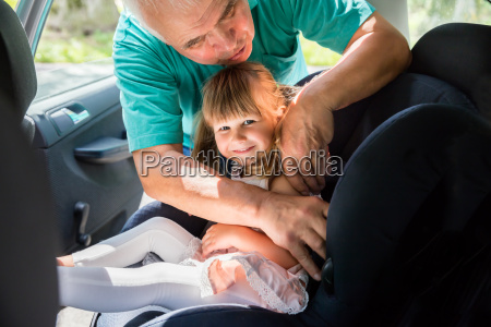 grandfather buckling up on granddaughter in