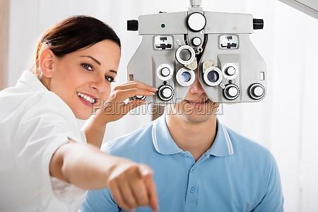 weibliche optometrist doing sehteste fuer patienten