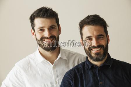 portrait of two bearded men smiling