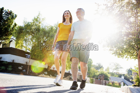 senior couple wearing shorts walking along