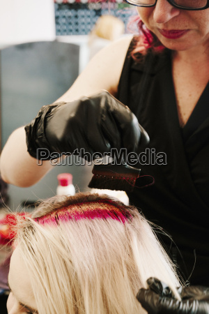 a hair colourist in gloves applying