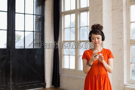 young woman wearing headphones standing in