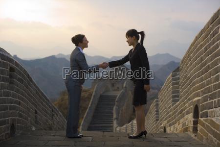 zwei geschaeftsfrauen schuetteln an der chinesischen