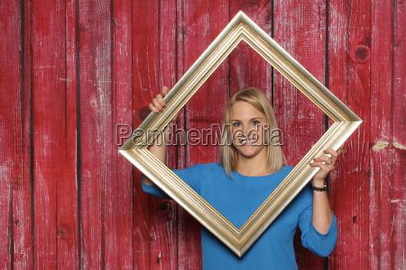 blondes maedchen schaut durch einen bilderrahmen