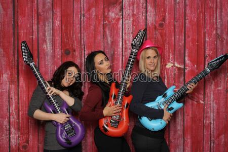 drei junge frauen spielen auf platikgitarren
