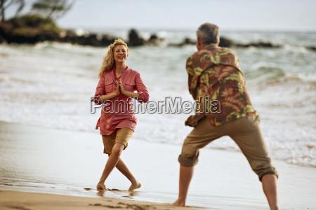 paar am strand spielerisch fotos voneinander