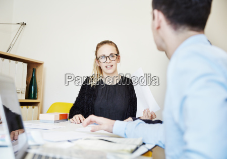 two people at a meeting seated
