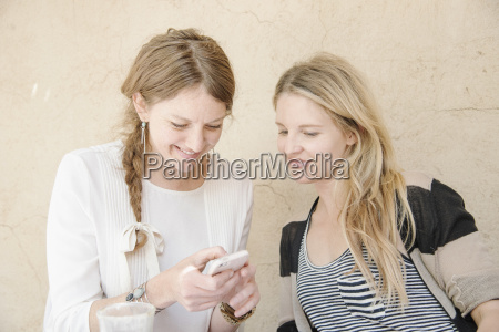 two smiling women with long blond