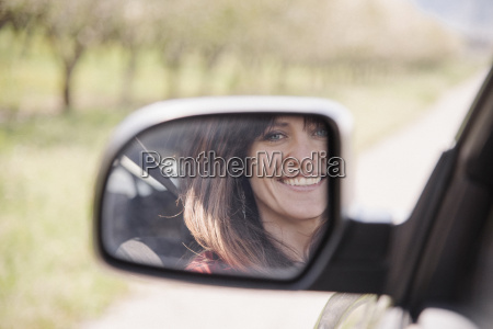 woman in a car smiling at