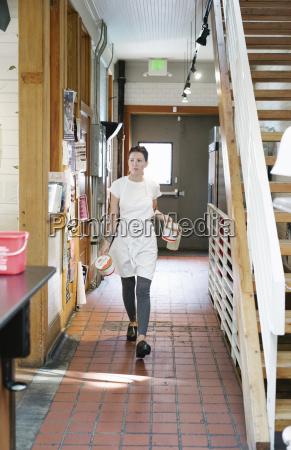 woman wearing an apron walking along