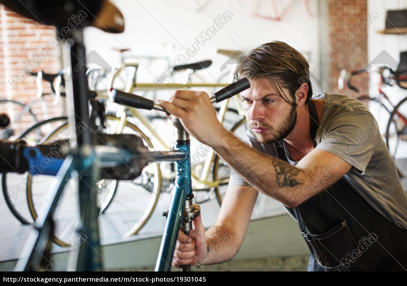 ein, mann, der, in, einer, fahrradwerkstatt, arbeitet - 19301045