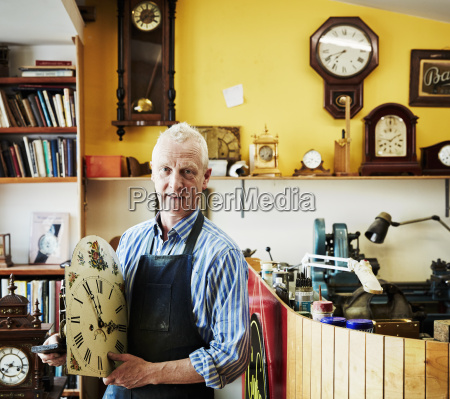 a clock maker showing off his